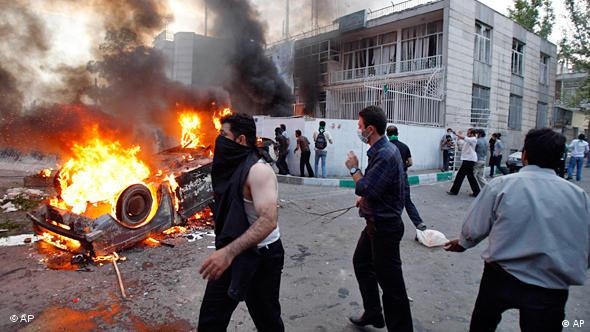 Protesters burn a car and attack a building of a pro-government militia base near a rally supporting leading opposition presidential candidate Mir Hossein Mousavi in Tehran, Iran, Monday, June 15, 2009.