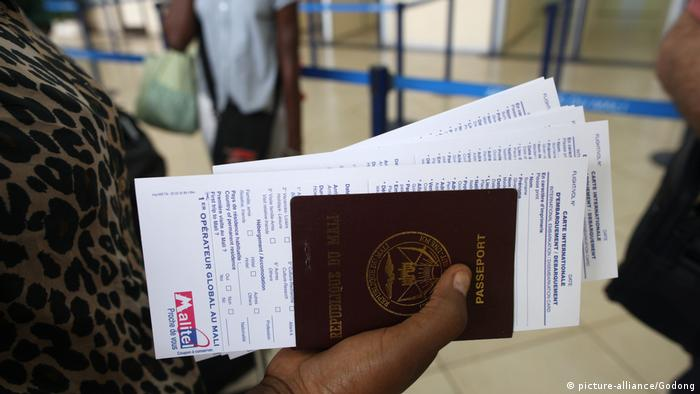A woman holds an African passport which is full of white forms