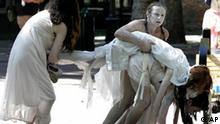 Bystanders look on with curiosity as Kaia Selene is carried by Ariel Denham, lower right, Alex Haverfield, center, and Vanessa Dkantze, left, through a park in downtown Seattle Monday, Sept. 11, 2006 as the group performs as Death Posture, a Butoh dance troupe based in Seattle, in conjunction with the installation of three sculptures made of salt in a downtown Seattle park that are dedicated to victims of the Sept. 11, 2001, terrorist attacks. The performance ended several blocks later. (AP Photo/Ted S. Warren)