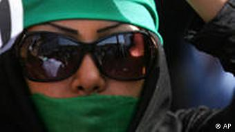 Picture of an Iranian woman wearing a green bandana and sunglasses with the lower half of her face painted green. (Photo: AP Photo/Ghalam News, HO)