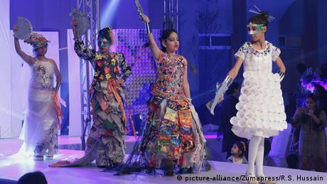 Photo: Models wear dress made from plastic at a fashion show (Source: picture-alliance/Zumapress/R.S. Hussain)