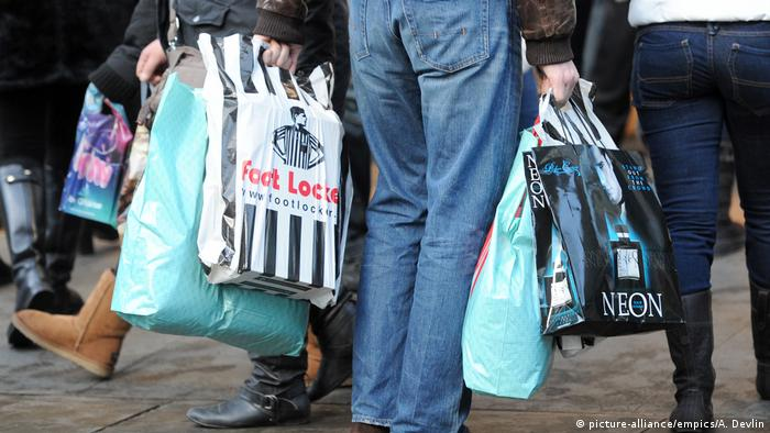 A person carriers five bags after a shopping spree