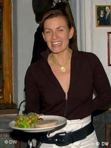 Anette Ueberschaer präsentiert mit einem lächelnden Gesicht ein Gericht (Foto: DW)