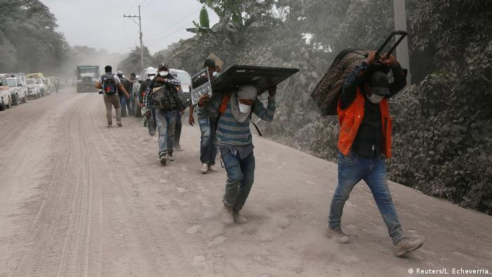 People carry stuff at an area affected by the eruption of the Fuego volcano in the community of San Miguel Los Lotes in Escuintla, Guatemala (Reuters/L. Echeverria)