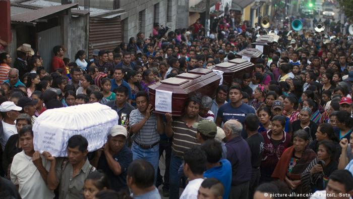 People carry the coffins of people who died during the eruption of Fuego volcano