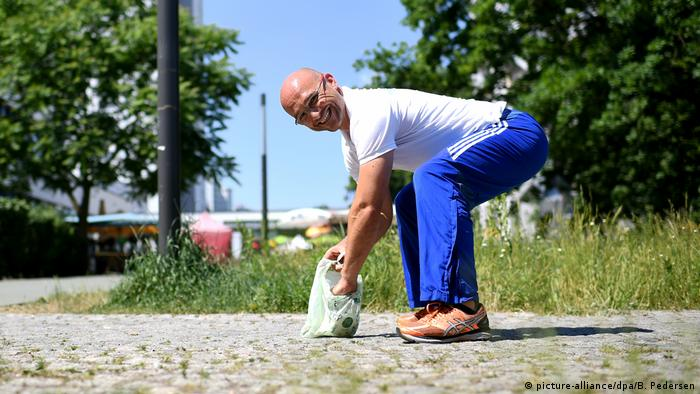 Deutschland, Berlin: Plogging-Aktion in Neukölln, Julian Grzybowski, Sportwissenschaftler zeigt Posen für Anfänger beim Plogging