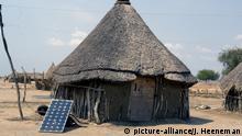 Solarzellen vor einer traditionellen Rundhütte - Tukol - in Yuai , Jonglei , Südsudan. | Verwendung weltweit