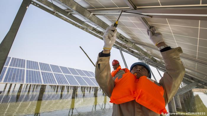 Homem instala painel fotovoltaico