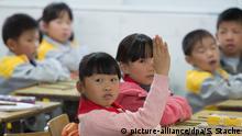 Menina chinesa ergue o braço em sala de aula com outros meninos e meninas.