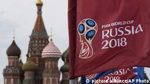 FILE - In this June 4, 2018, file photo, a flag with the logo of the World Cup 2018 on display with the St. Basil's Cathedral in the background, in Moscow, Russia. If you're looking for the favorite when the World Cup opens in Russia, it's Brazil. Spain will be the losing finalist. If real outsiders are of interest, two to keep in mind might be Latin American teams Colombia and Peru. (AP Photo/Pavel Golovkin, File)  