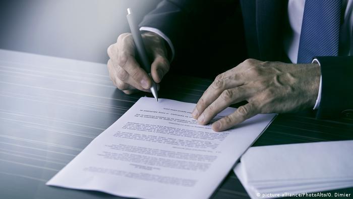 Менеджер подписывает документ