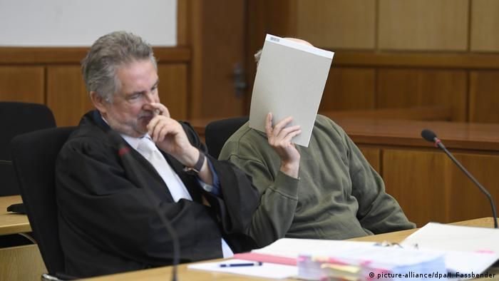 The defendant covers his face in court