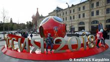 People gather near decorations for the upcoming 2018 FIFA World Cup, with St. Basil's Cathedral seen in the background, in central Moscow, Russia June 7, 2018. REUTERS/Sergei Karpukhin