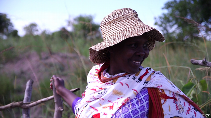 A woman in rural Uganda wearing a straw hat smiles and looks off to the side
