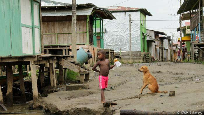 A boy and a dog on a dirt road between shacks in Riosucio, Colombia