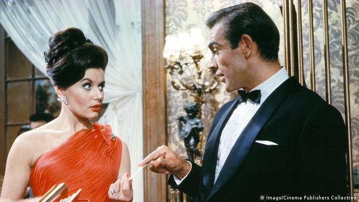 یوبنیس گیسون در نخستین فیلم از مجموعه فیلمهای جیمز باند با عنوان دکتر نو (۱۹۶۲ میلادی) خود را سر میز قمار اینگونه معرفی میکند: «ترنچ. سیلویا ترنچ». سپس هنگامی که او نام مأمور مخفی ۰۰۷ را میپرسد، پاسخ شان کانری برای همیشه به مُهر فراموشنشدنی این مجموعه فیلمها تبدیل میشود: «باند. جیمز باند». گیسون یک سال بعد در نقش باند گرل در کنار شان کانری در فیلم از روسیه با عشق حضور یافت.