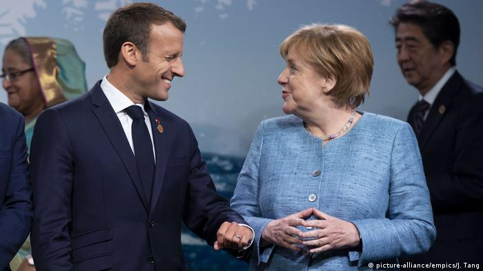 French President Emmanuel Macron jokes with German Chancellor Angela Merkel during a family photo at the G7 summit in Quebec, Canada