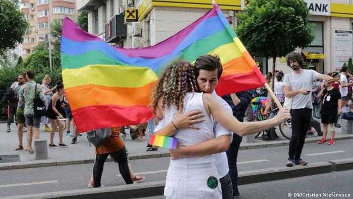 Two people hugging with a rainbow flag in Bucharest Pride 2018