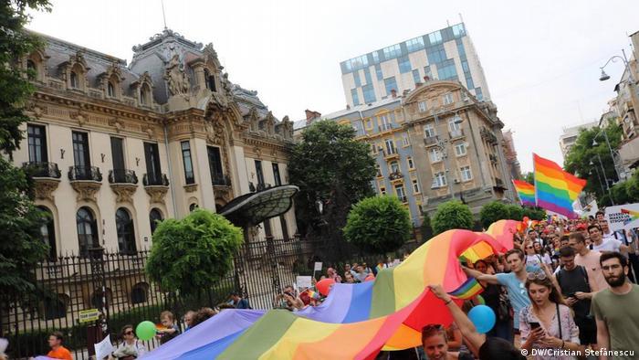 Marchers under a rainbow flag