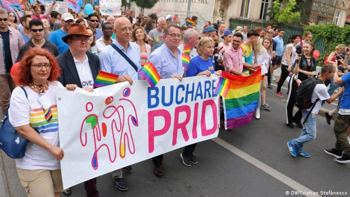 Parade participants holding Bucharest Pride banner
