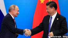 China's President Xi Jinping and Russia's President Vladimir Putin shake hands during Shanghai Cooperation Organization (SCO) summit in Qingdao, Shandong Province, China June 10, 2018. REUTERS/Aly Song