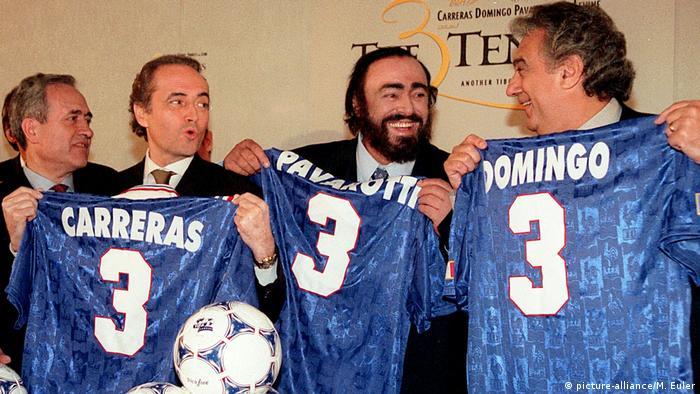 Jose Carreras, Luciano Pavarotti und Placido Domingo (von links) halten Fußballtrikots hoch, die ihren Namen tragen