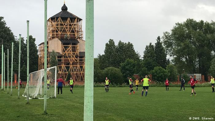 Fedino's football club faces off against another local club against the backgrond of a small church (DW/E. Sherwin)