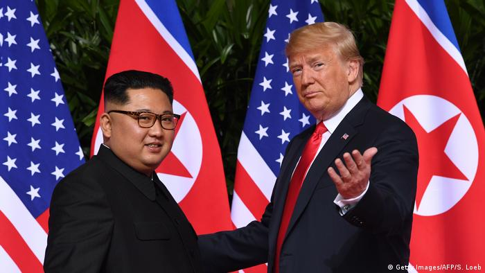 US President Donald Trump (R) gestures as he meets with North Korea's leader Kim Jong Un (L) at the start of their historic US-North Korea summit