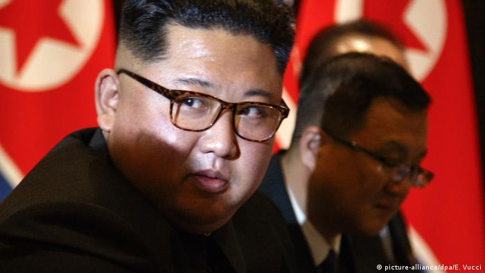 North Korea leader Kim Jong Un looks at the news media during a photo session