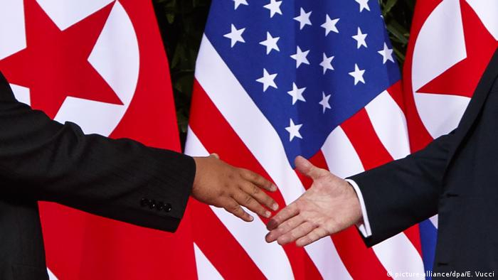 U.S. President Donald Trump, right, reaches to shakes hands with North Korea leader Kim Jong Un