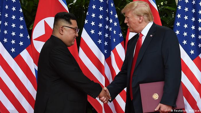 U.S. President Donald Trump and North Korea's leader Kim Jong Un shake hands during the signing of a document after their summit at the Capella Hotel on Sentosa island in Singapore June 12, 2018 (Reuters/A. Wallace)