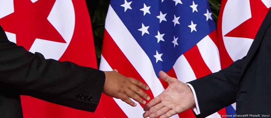 Líder norte-coreano Kim Jong-un (e.) estende a mão para cumprimentar o presidente americano Donald Trump