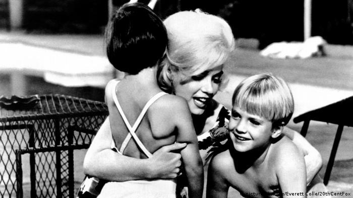 Imagem em preto e branco mostra Marilyn Monroe abraçada a duas crianças durante filmagens de 'Something's Got To Give'