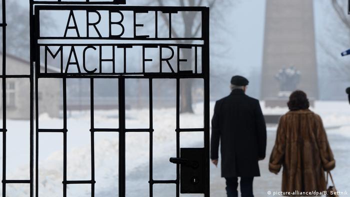 Hermann Höllenreiner and his wife Else walk through the gates of Sachsenhausen in winter