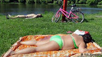 Photo: Muscovites sunning themselves in a city park. Source: RIA Novosti