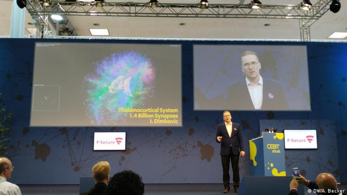 Picture of Mikko Hippönen on a stage and on a screen at CEBIT