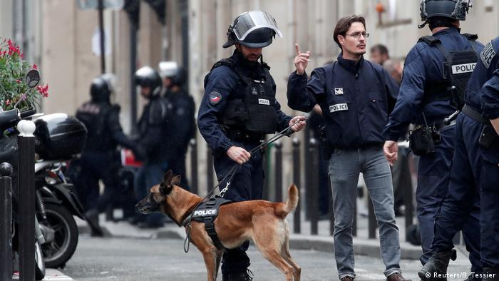 French police with their dog secure the street near the office where a man has taken people hostage.