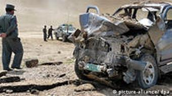 Afghan Police inspect a damaged vehicle of an aid organization after it hit a road side bomb in Kunduz