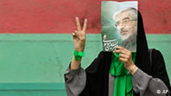 An Iranian demostrator holding up a picture of Moussawi