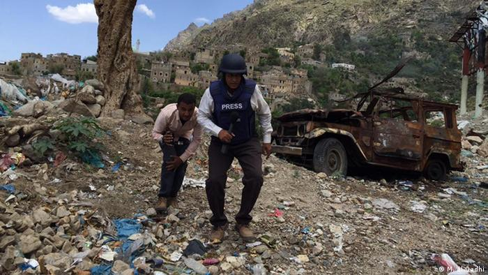 Two journalists next to a bombed-out vehicle in Taiz (M. al-Qadhi)
