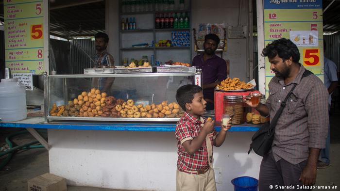 A boy and father drink tea at a tea stand in Tamil Nadu, India