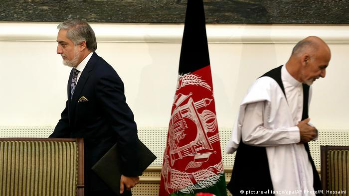 Afghanistan's then presidential election candidates Abdullah Abdullah, left, and Ashraf Ghani, right, leave after signing a power-sharing deal at presidential palace in Kabul