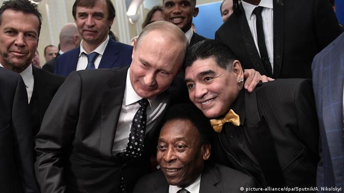 Pelé sentado, junto a Vladimir Putin, Maradona e outros homens de paletó