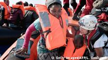 A woman with her child are helped to board a dinghy of the rescue team off Libyan coast on May 12, 2018. - The 74 migrants of various nationalities, including women and children were rescued by MV Aquarius, a rescue vessel chartered by SOS-Mediterranee and Doctors Without Borders (MSF). (Photo by LOUISA GOULIAMAKI / AFP) (Photo credit should read LOUISA GOULIAMAKI/AFP/Getty Images)