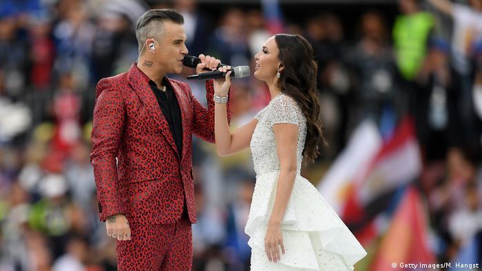 رابی ویلیامز (چپ)، ستاره معروف بریتانیایی، به همراه آیدا گاریفولینا، خواننده اپرا از روسیه، در مراسم افتتاحیه ۲۰۱۸ روسیه هنرنمایی کردند و با صدای خود تماشاگران حاضر در ورزشگاه را به وجد آوردند.