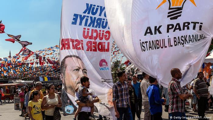 People hold an election poster showing Turkey's president