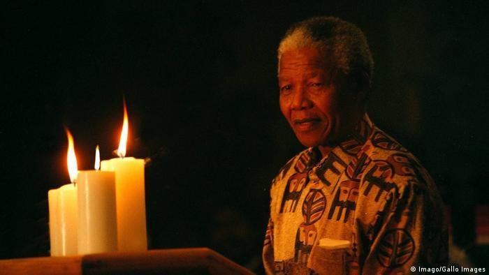 Nelson Mandela olha para velas acesas sobre uma mesa no Contry Club de Johannesburgo em 1996