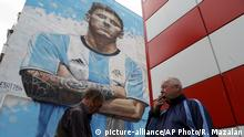 Men share a smoke under a mural of Argentina's soccer star Lionel Messi during the 2018 soccer World Cup in Bronnitsy, Russia, Thursday, June 14, 2018. (AP Photo/Ricardo Mazalan) |