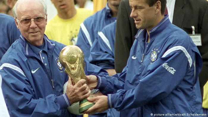 Der brasilianische Trainer Mario Zagallo (l) und Mannschaftskapitän Carlos Dunga (r) tragen am 04.06.1998 in Paris gemeinsam den Fußball-Weltpokal. (picture-alliance/dpa/A.Scheidemann)