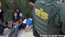 12.06.2018 +++ MCALLEN, TX - JUNE 12: Central American asylum seekers wait as U.S. Border Patrol agents take them into custody on June 12, 2018 near McAllen, Texas. The families were then sent to a U.S. Customs and Border Protection (CBP) processing center for possible separation. U.S. border authorities are executing the Trump administration's zero tolerance policy towards undocumented immigrants. U.S. Attorney General Jeff Sessions also said that domestic and gang violence in immigrants' country of origin would no longer qualify them for political asylum status. (Photo by John Moore/Getty Images)